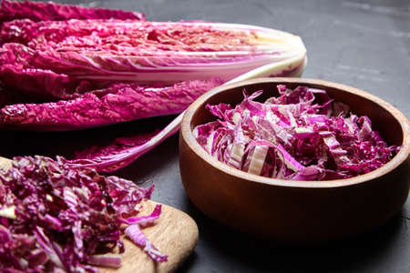 Chopped Red Chinese cabbage (Purple wombok) on wooden cutting board and bowl on stone table. Red Napa cabbage with vibrant colored leaves on black background. Cooking vegetable salad, healthy food Reklamní fotografie