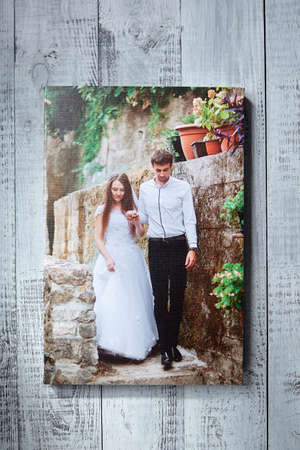 Photo canvas print. Sample of stretched wedding photography, front view. Bridal portrait hanging on gray wooden wall