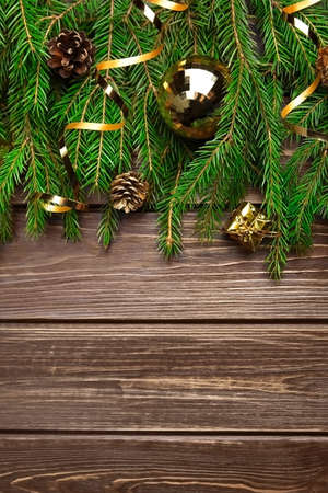 Fir tree branches with christmas decorations on wooden background