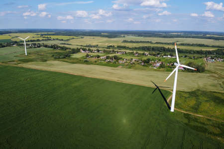 Wind energy, windfarm. Aerial view of wind turbines and green agricultural field and village. Wind power, sustainable and renewable energy Archivio Fotografico