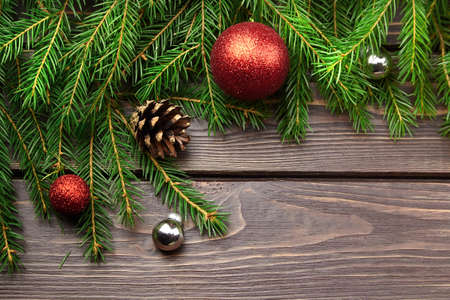 Christmas and New Year decorations with fir tree branches on dark wooden background. Christmas composition with red balls and cones
