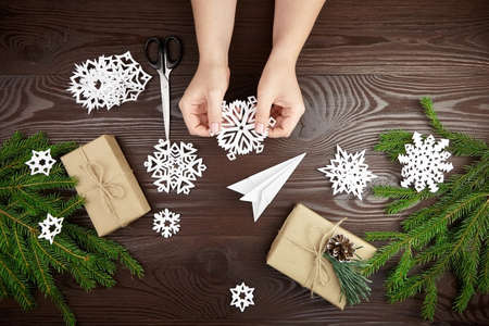 Hands holding white paper snowflake over wooden table