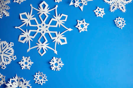 Composition with white paper snowflakes on blue background Archivio Fotografico