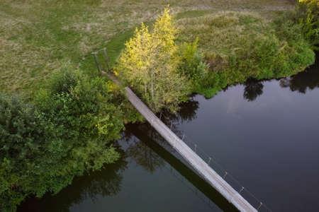 Suspension bridge over a small river, aerial view. Hanging bridge across river. Summer landscape