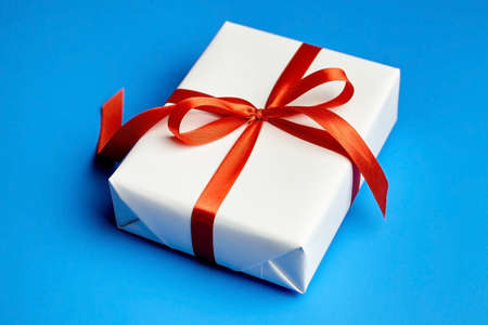 White gift box tied with red ribbon on blue background