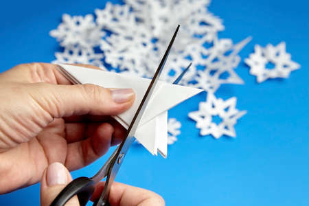 Hands cutting white paper snowflakes over blue background Archivio Fotografico