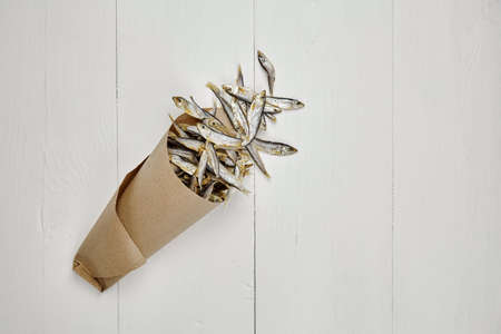 Dried small salted sprat or kilka fish in paper bag on white wooden table background. Top view, copy space.