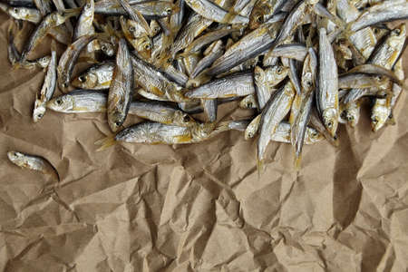 Dried small salted fish stack on crumpled parchment paper background. Top view, copy space.