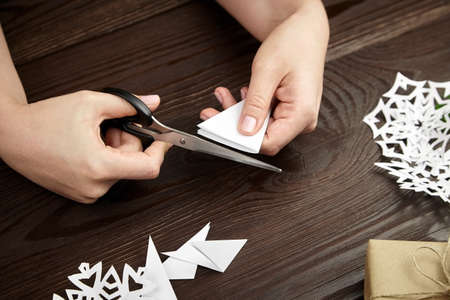 Hands cutting white paper snowflakes over wooden table