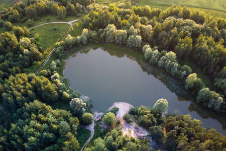 Aerial view - small lake in a forest and field, sunset light. European nature.