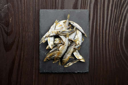 Small salted dried sprat or tulka fish heap on balck slate board over dark wooden table background. Top view.