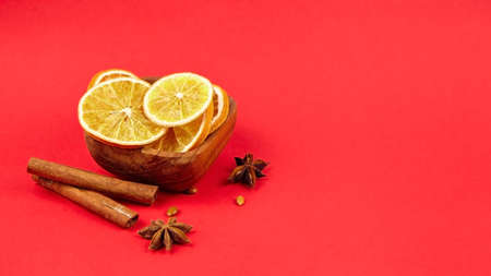 Dried orange slices in wooden bowl with cinnamon sticks and anise stars spices on red background.