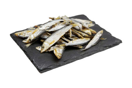 Small dried fish on black slate board isolated on white background. Beer snack.