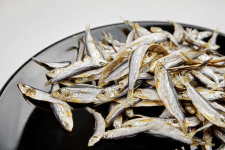 Dried salted small fish on black plate background. Beer snack. Archivio Fotografico