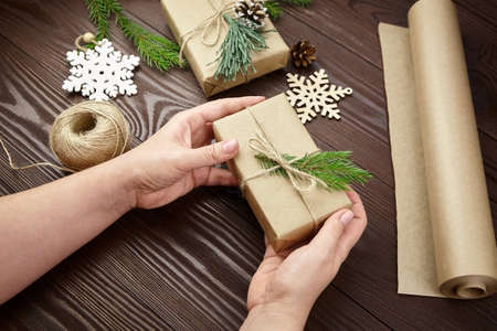 Woman decorating Christmas presents over wooden table Archivio Fotografico