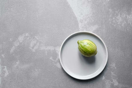 The variegated pink lemon or pink-fleshed Eureka lemon in plate on concrete background with copy space, top view. Citrus fruit with green-striped rind Archivio Fotografico