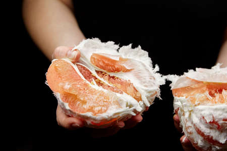 Pomelo citrus fruit with sweet red flesh on black background. Fresh juicy shaddock (Citrus maxima), closeup. Peeled pomelo in a female hand. Healthy fruit