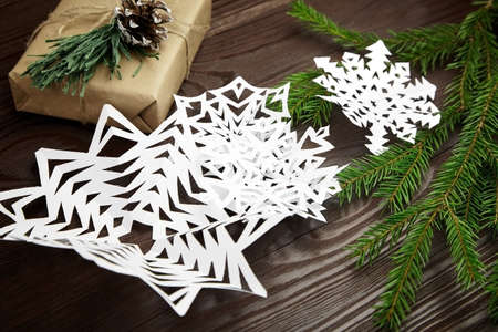White paper snowflakes, gift box and fir tree branch on wooden table Archivio Fotografico