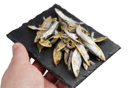 Small dried fish on black slate board in a hand isolated on white background