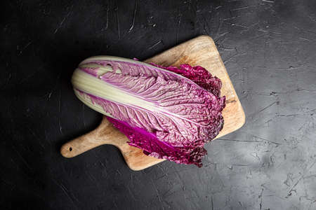 Wooden cutting board with Red Chinese cabbage (Purple wombok) on black stone background. Red Napa cabbage with vibrant colored leaves, healthy vegetable, top view. Asian cuisine