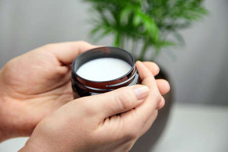 Organic shea butter in jar, natural moisturizing cosmetics, skin and hair care product. Anti-aging treatment.