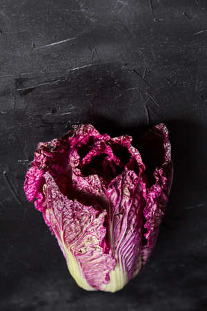 Red Chinese cabbage (Purple wombok) on black stone background. Red Napa cabbage with vibrant colored leaves