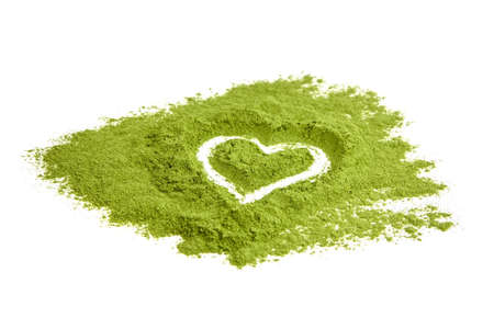 Freeze dried wheatgrass powder heart isolated on white background. Herbal medicine, detox food supplement.