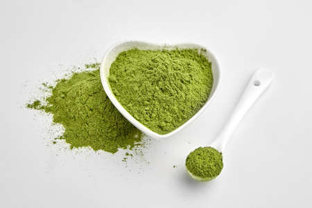 Organic wheatgrass or barley grass powder in ceramic bowl and spoon on white. Detox superfood measuring. Vegan-friendly supplement.