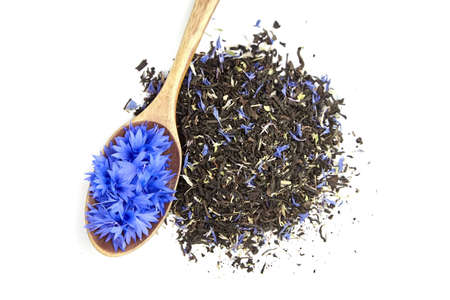Black and herbal tea blend with fresh blue cornflower petals in wooden spoon isolated on white background, top view