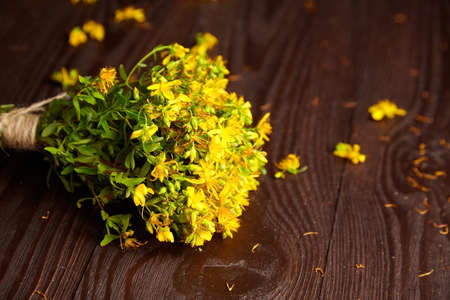 Bouquet of St. John's wort (Hypericum perforatum), flowering plant with yellow flowers, healing herb on wooden table. Alternative medicine, herbal remedy Archivio Fotografico