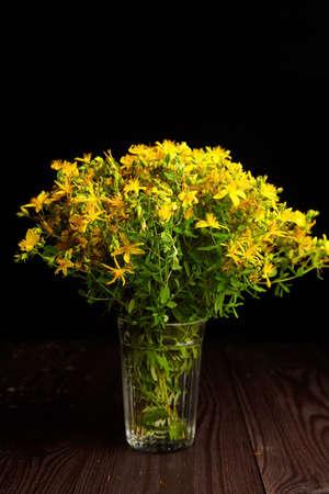 Hypericum perforatum flowers bouquet in glass on dark wooden table background