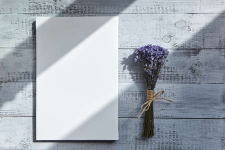 White blank canvas and bouquet of lavender flowers on wooden table with a shadow from the sunlight covering. Mockup, top view
