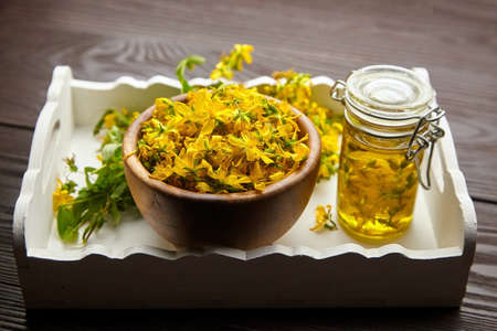 Glass jar with hypericum or St Johns wort oil extract and wooden bowl with fresh flowers on white wooden tray. Herbal medicine. Archivio Fotografico
