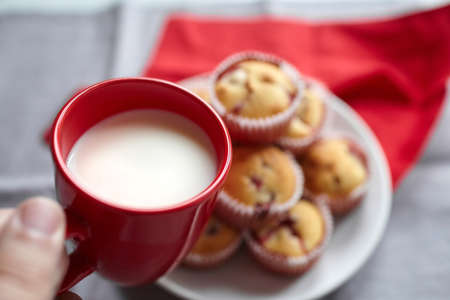 Cup of milk in hand with homemade strawberry muffins, healthy sweet summer dessert