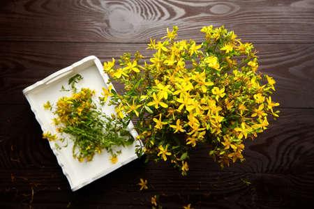 Bunch of medicinal herbs - Hypericum perforatum or St johns wort herb harvesting, dark wooden background, herbal treatment, top view