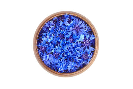 Medicinal herb - blue fresh cornflower petals in wooden bowl isolated on white background, top view. Alternative herbal medicine.