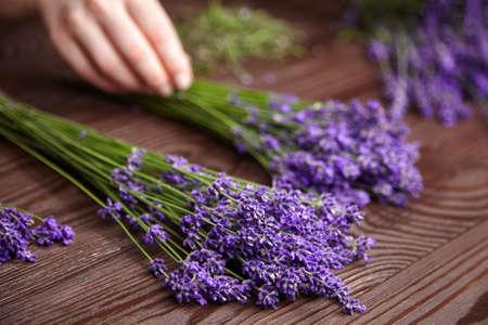 Florist sorting fresh lavender flowers for making a lavender bouquet on dark wooden background.