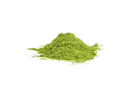 Green freeze dried wheatgrass powder heap isolated on white background.