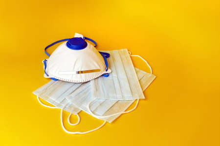 Respirator and surgical masks on yellow background. Disposable medical face masks. Airborne disease protection, COVID-2019, coronavirus pandemic