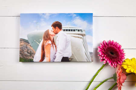 Canvas print with gallery wrap technique on white wooden table, top view. Wedding photo and bouquet of gerbera flowers. Stretched photography. Portrait of kissing couple. Memories of a romantic cruise