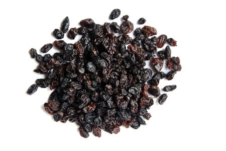 Raisins isolated on white background, top view. Heap of dried red grapes, selective focus
