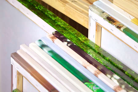 ? anvas prints, stack of colorful photos with gallery wrapping method of canvas stretching on wooden stretcher bars. Samples of stretched photo canvases. Staple mount, edges, side view Reklamní fotografie