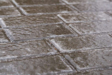 Ice crusted ground, paving slabs surface covered ice, slippery street, winter weather. Icy sideway Archivio Fotografico