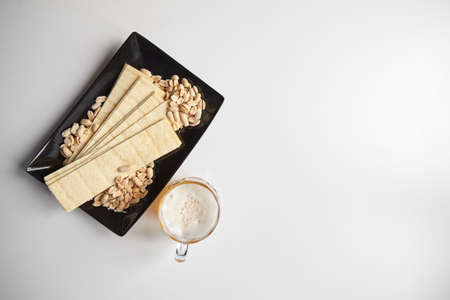 Mug of unfiltered light wheat beer with beer snacks on white table, top view. White unfiltered beer, long potato chips, salted roasted peeled peanuts in black plate, selective focus