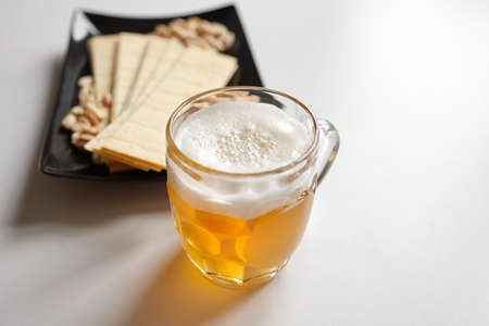 Mug of unfiltered light wheat beer with beer snacks on white table. White unfiltered beer, long potato chips, salted roasted peeled peanuts in black plate, selective focus