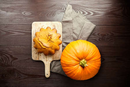 Pumpkin autumn holiday sweet cake with fresh pumpkin on wooden rustic background with linen napkin, top view Stock fotó