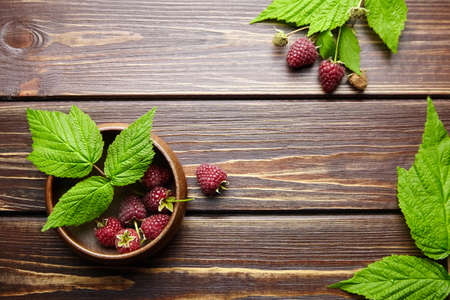 Fresh raspberry red berries with green leaves in bowl on wooden table background with copy space, ripe juicy raspberries top view