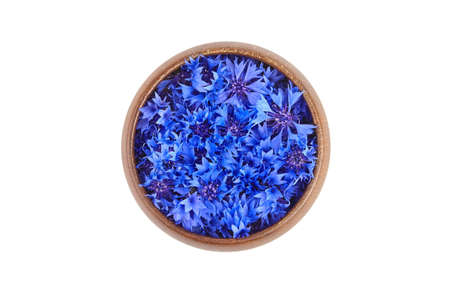 Blue fresh cornflower buds in wooden bowl isolated on white background, top view. Alternative herbal medicine.