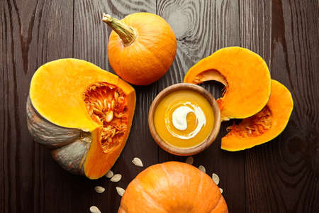 Autumn food flat lay - pumpkin cream soup in wooden bowl with fresh pumpkins on dark background. Top view.