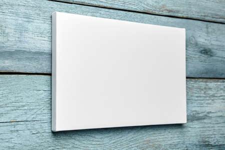 White canvas hanging on light blue wooden wall. Mockup, wall decor, blank canvas stretched on stretcher bar, side view Stock fotó